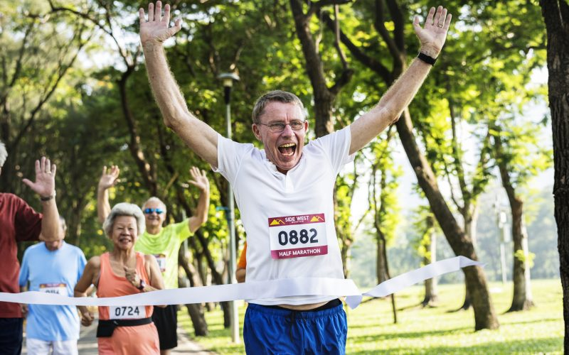Happy senior running through the finish line